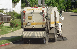 photo of City of Oakland street sweeper cleaning a residential street