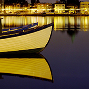 photo of yellow boat reflecting on Lake Merritt