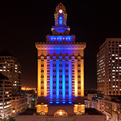 photo of historic Oakland City Hall awash in blue and gold light supporting the Golden State Warriors
