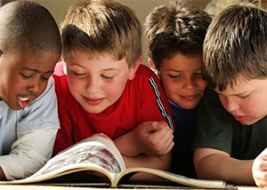 Photo of four boys reading together at school