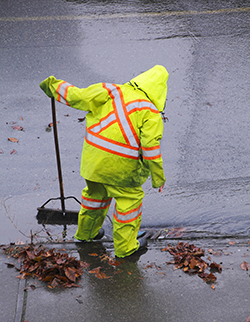 Photo of person clearing out storm drain to prevent street flooding