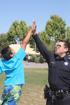 Photo of officer high fiving a youth