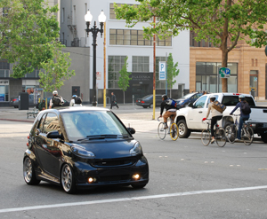 photo of small car and bicyclists