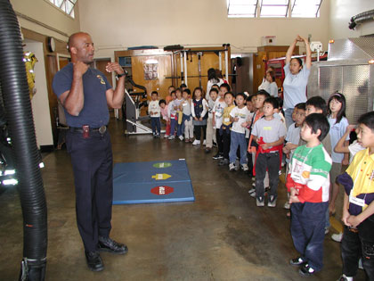 photo of Oakland firefighter teaching children exercise