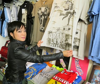 Photo of Loretta Nguyen, owner of Loakal Art Gallery and Boutique, displaying some of her unique Oakland t-shirts.