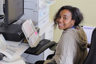 Photo of a smiling young woman at a computer, one of the Mayor's Summer Jobs Program participants