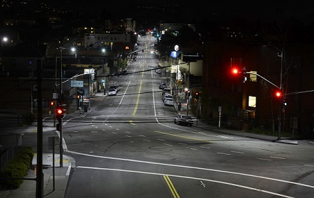 Photo of a commercial district intersection at night after the installation of LED streetlights, with the streets and sidewalks well-illuminated