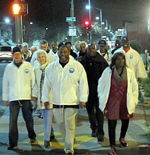 Photo of volunteer members of Operation Ceasefire crossing the street and smiling during a night-walk.